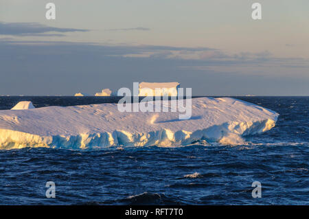 Antarctic Sunset: Floating Icebergs in the Weddell Sea, near the Antarctic Peninsula, as seen from an Antarctic Exploration Ship - Stock Photo