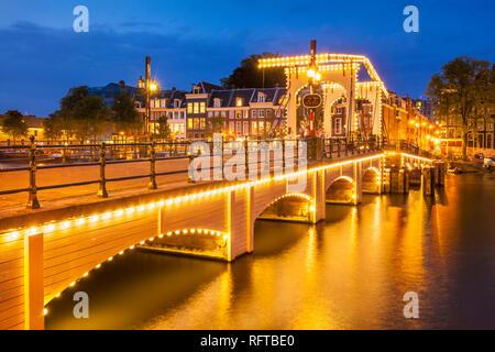 Illuminated Magere brug (Skinny Bridge) at night spanning the River Amstel, Amsterdam, North Holland, Netherlands, Europe - Stock Photo