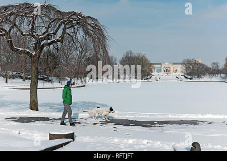 Cleveland, Ohio, USA. 26th Jan, 2019.  A man and his dog walk around Wade Park Pond, frozen over by the arctic cold temperatures engulfing the region.  The cold air is forecasted to go much lower in the coming week.  Credit: Mark Kanning. Credit: Mark Kanning/Alamy Live News - Stock Photo