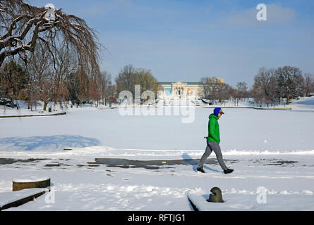Cleveland, Ohio, USA.  26th Jan, 2019.  A man walks around the frozen Wade Park Pond in Cleveland, Ohio, USA as arctic temperatures engulf the city.  The Cleveland Museum of Art is in the far background.  Credit: Mark Kanning. Credit: Mark Kanning/Alamy Live News - Stock Photo