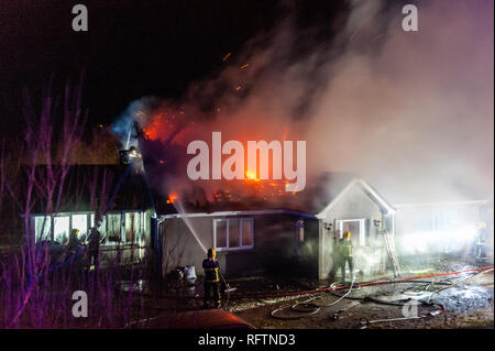 Bantry, West Cork, Ireland. 27th Jan, 2019. Firemen and locals battle to save a house from being totally destroyed by fire earlier this morning. Six fire appliances attended the fire with dozens of firefighters and Gardai also on the scene. No injuries were reported in the blaze. Credit: Andy Gibson/Alamy Live News. - Stock Photo
