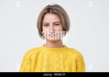 Cunning beautiful woman in yellow sweater indenting to realize tricky plan. Attractive female having sly expression - Stock Photo
