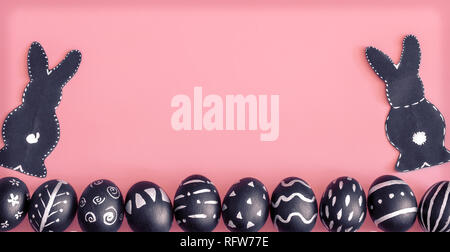 Easter composition from eggs of the black colors with creative light pattern, handmade in a round nest made of hay ,and the Easter Bunny in black colo - Stock Photo