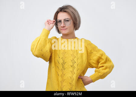 Girl in yellow sweater cannot read sign putting on glasses squinting and frowning, trying understand what written, having problems with sight - Stock Photo