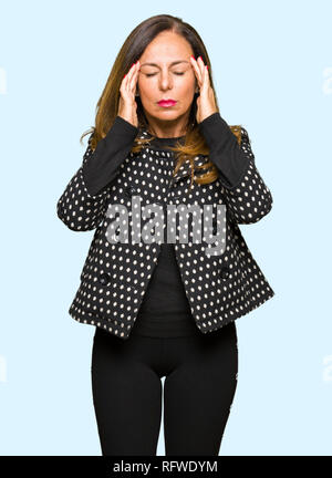 Beautiful middle age woman wearing fashion jacket with hand on head for pain in head because stress. Suffering migraine.