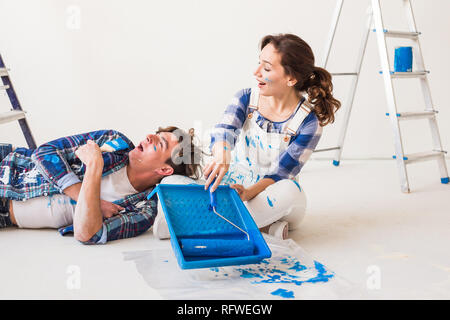 Smiling loving couple doing home renovations. Young woman is holding a paint roller and young man is resting - Stock Photo
