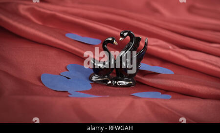 figures of two black swans on a red background. - Stock Photo