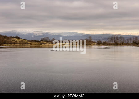 View across beautiful, semi frozen lake with snowflakes on new ice and reed and distant snow-capped mountains from the other side - Stock Photo