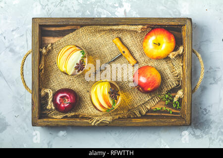 Glasses of homemade organic apple cider with fresh apples in box, top view, light gay concrete table surface. - Stock Photo