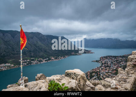 Kotor, Montenegro - April 2018 : National flag of Montenegro fluttering in the wind on top of the ruins of the St John fortress located above Kotor to - Stock Photo
