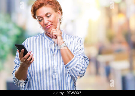 Atrractive senior caucasian redhead woman texting using smartphone over isolated background serious face thinking about question, very confused idea - Stock Photo