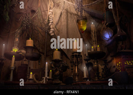 A  pirate's lair with glowing candles and mysterious artifacts are one of the sights to see upon exiting the Pirates of the Caribbean ride. - Stock Photo