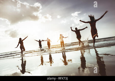 Big group of happy friends runs and jumps at sunset beach. Six active silhouettes against sea beach - Stock Photo