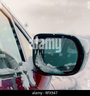 A side mirror of a car in the snow on a winter day - Stock Photo