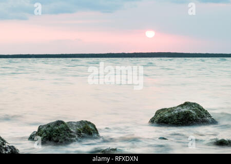 Sunset in Islamorada, Florida Keys with pink sky and sun by green water rocks closeup on gulf of Mexico or Atlantic Ocean and horizon - Stock Photo