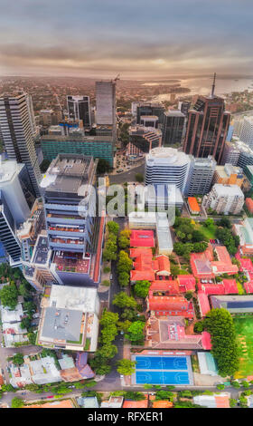 Aerial view over roof tops of tall modern urban high-rise towers around North Sydney post office 2060 from ground level to sky and distant Sydney Harb - Stock Photo