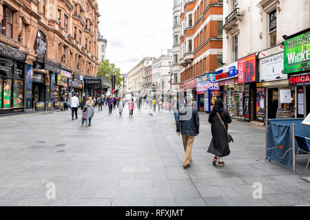 London, UK - September 12, 2018: Many people tourists walking on sidewalk street shopping at Leicester Square stores during day in city - Stock Photo