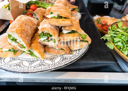 Closeup of fresh display of stacked pile of panini bread mozzarella melted cheese sandwiches and vegetarian italian arugula in store shop cafe buffet  - Stock Photo