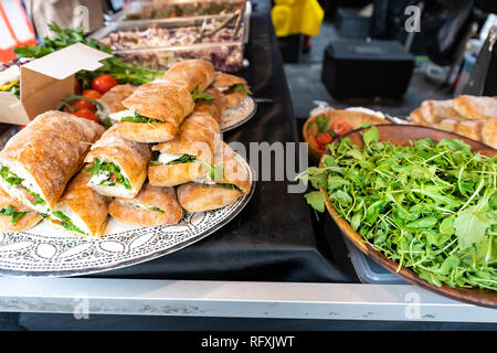 Fresh display of pile of panini bread mozzarella melted cheese sandwiches and vegetarian italian arugula in store shop cafe buffet catering - Stock Photo