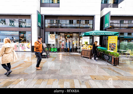 London, UK - September 12, 2018: Whole Foods Market Wholefoods store shop entrance with people on Glasshouse street with rainy wet day in Soho - Stock Photo