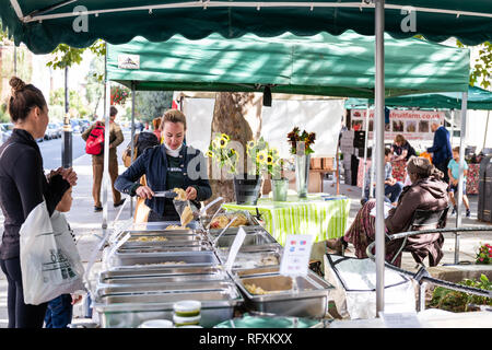 London, UK - September 15, 2018: Neighborhood market in Pimlico with people walking by food buffet on street road and vendor