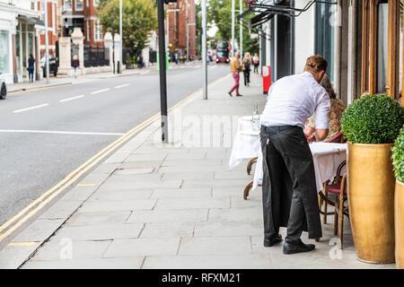 London, UK - September 16, 2018: Man waiter standing setting up cafe table in Chelsea outside restaurant street sidewalk during day - Stock Photo