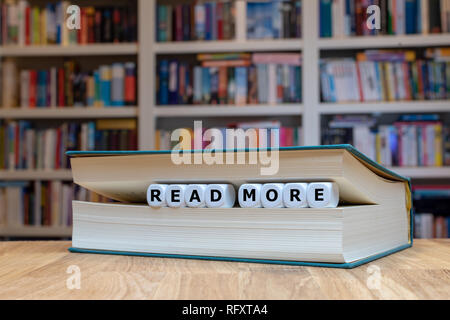 Dice in a book form the words 'read more'. Book is lying on a wooden desk infront of a bookshelf. - Stock Photo
