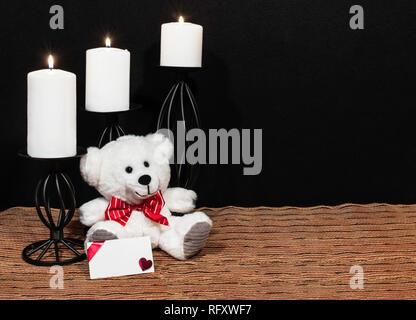 Cudlely teddy bear with red bow tie, white candles perched on black candle holders on mesh place mat and wooden table with card and dark background. V - Stock Photo