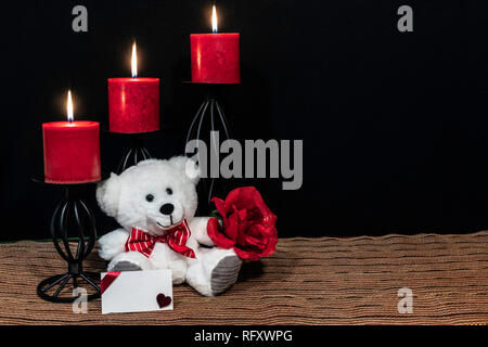 Cudlely teddy bear with red bow tie, red rose, red candles perched on black candle holders on mesh place mat and wooden table with card and dark back - Stock Photo