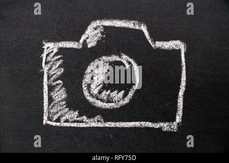 White chalk hand drawing as camera icon on black board background - Stock Photo