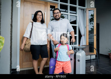 family with suitcase standing in front of their house  - Stock Photo