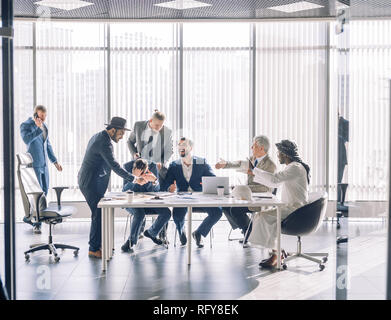 Multiracial partners dispute at negotiations, having fun while settling conflict - Stock Photo