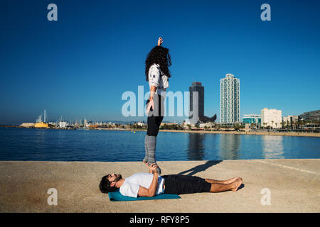 Beautiful couple practicing acro yoga in the morning - Stock Photo