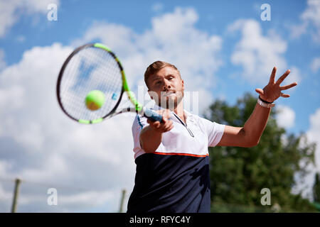Young man in sportwear is playing tennis on out door court. - Stock Photo