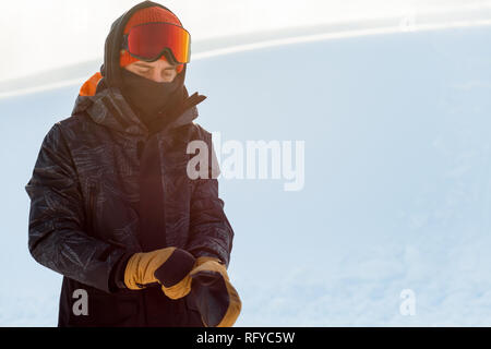 Young snowboarder in sportswear putting on his gloves before snowboarding - Stock Photo