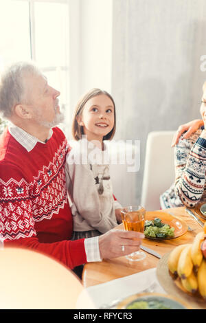 cheerful beautiful girl is sitting on her granny's legs and looking up - Stock Photo