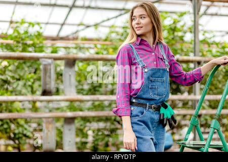 Happy female girl standing in the ladder in garden in summer - Stock Photo