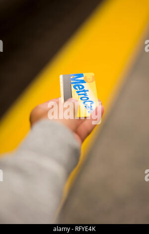 NEW YORK, UNITED STATES - AUGUST 27, 2017: Hand with MetroCard in New York City. Metrocard allows you to travel on New York City public transport. - Stock Photo