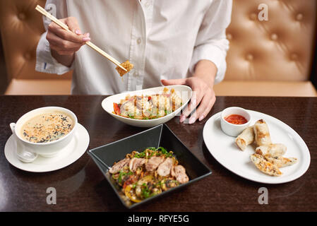 Girl in white blouse sitting in luxury restaurant and eating tasty meal. Three courses lunch from soup, noodles and tempura shrimps on special offer.  - Stock Photo