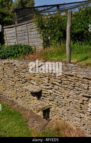 Dry stone wall with stile built in to access raised garden.Thin Cotswold limestone creates a neat even strong wall.North Wiltshire.England. - Stock Photo