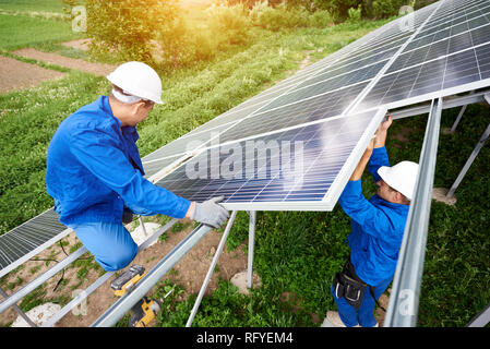 Installing of stand-alone solar photo voltaic panel system. Two technicians in hard-hats mounting big shiny solar module on platform on green summer v - Stock Photo