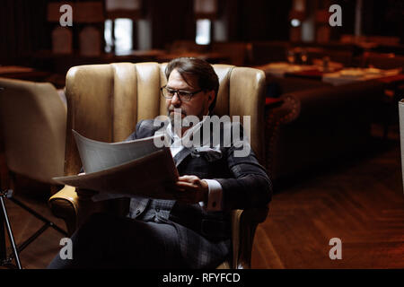 Mid-aged well-dressed man sitting in arm-chair in living room reads newspaper