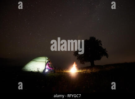 Night camping in mountains. Young pretty tourist girl sitting in entrance of lit from inside tent watching brightly burning bonfire under beautiful de - Stock Photo