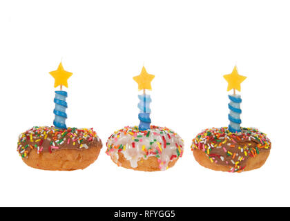 Vanilla cake donuts with white and chocolate frosting and colorful candy sprinkles lined up side by side, Blue decorative candles with stars on top is - Stock Photo