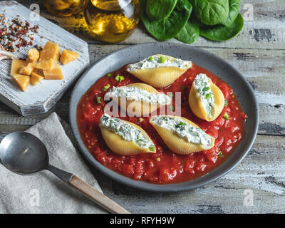 cooked pasta conchiglioni stuffed spinach and cheese, tomato sauce on plate - Stock Photo