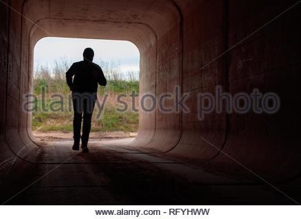 man running through dark tunnel escaping - Stock Photo