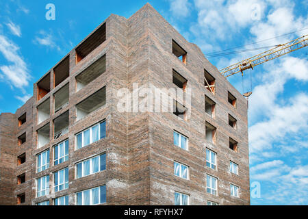 construction of a new multi-storey residential building in the city on summer - Stock Photo