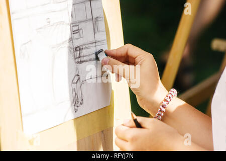 artist drawing a pencil on the street on sunny summer day. hand closeup - Stock Photo