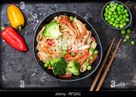 Vegetable stir fry with udon noodles, broccoli, carrot, pepper and green peas in bowl on black background. Top view - Stock Photo