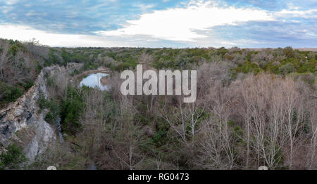 View of Small Lake and Dense Covered Area Next to Dam - Stock Photo